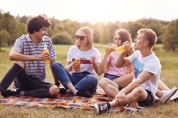 Horizontal shot of happy friends have picnic, drink cold beer, enjoy summer weather, sit on plaid, share latest news, pose against green nature background. Youth, lifestyle and free time concept
