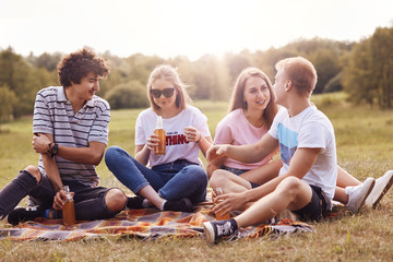 Four friendly youngsters spend free time outdoor, sit on plaid, have pleasant talk, drink cider, have pleasant smiles. Two coulpes have picnic outside. Friendship, companionship, relationship concept