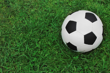 soccer black and white ball on the green grass, top view.