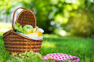 Fotobehang Picknick Picnic basket with vegetarian food in summer park