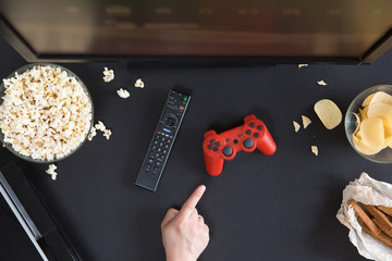 Top view of gamer and TV accessorises and snacks frame, flat lay on black background with copyspace. Joystick and gamepad, keyboard, game console, beer, chips and popcorn. Game or film choice