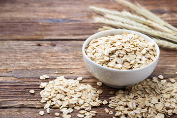 Dry rolled oat flakes oatmeal on wooden table