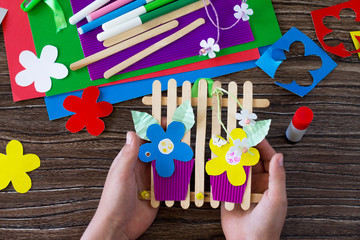 A gift of summer flowers on wooden sticks a fence on a wooden table. Handmade. Project of children's creativity, handicrafts, crafts for kids.