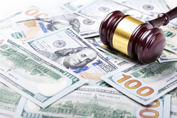 Wooden judge gavel on hundred dollar banknotes background