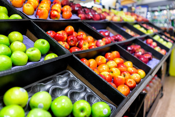 Many varieties assorted red apples on display shelf in grocery store boxes in aisle, supermarket inside, nobody, including granny smith green