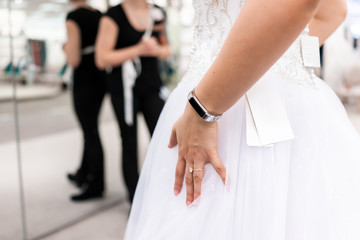 Closeup back of young woman trying on wedding dress in boutique discount store with shiny tulle, price tag, engagement ring, fitness watch