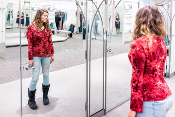 Young woman trying on clothing jeans in boutique store looking at herself in mirror with red shirt and boots