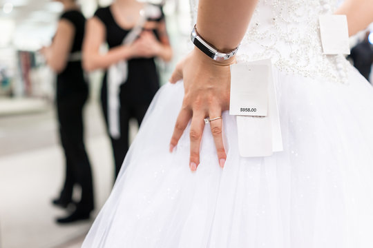 Closeup back of young woman trying on wedding dress in boutique discount store with shiny tulle, expensive dollars price tag, engagement ring, fitness watch