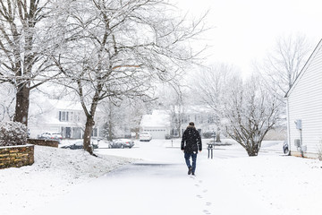 Man walking in driveway in neighborhood with snow covered ground during blizzard white storm, snowflakes falling in Virginia suburbs, single family homes to check mail in mailbox