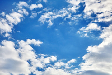 white fluffy soaring clouds on a blue sky background