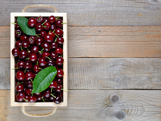 Cherry in box on wooden table top view