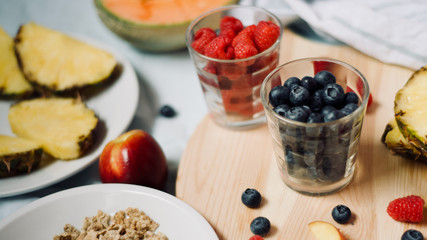 tasty healthy eating vegetarian vegan detox breakfast with fresh seasonal fruits and berries served on chopping board over pastel blue background