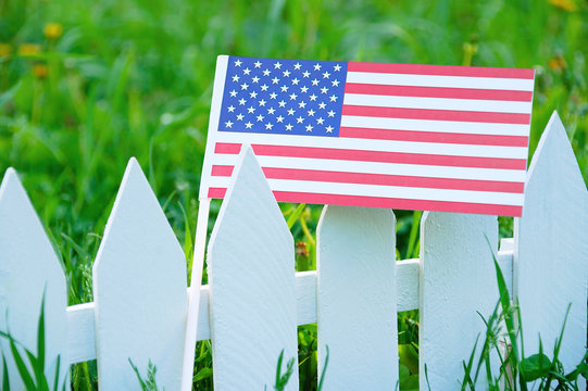 The US flag on a white fence against the background of a blooming green grass.
