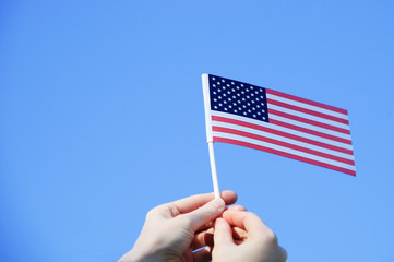 The US flag in the hands against the blue clear sky. Close-up.