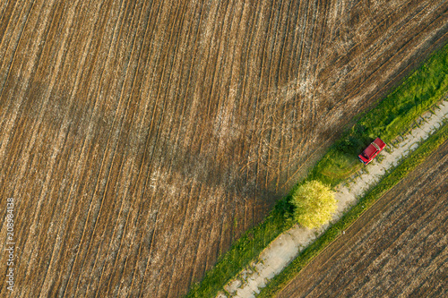 Wall mural Aerial view from the drone, a bird's eye view of agricultural fields with a road through and red car on it in the spring evening at sunset
