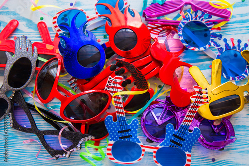 f7c882ad46d Set of colorful party sunglasses icons. Funny fashion glasses accessories.  Collection of colorful sunglasses on blue wooden background.