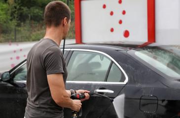 Man washing car outdoors