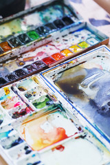 Hobbies and education, a cuvette with different watercolors.