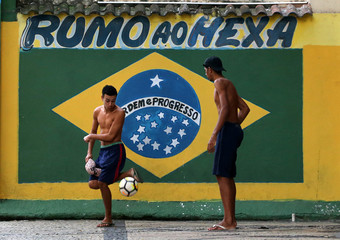 Residents play soccer next to a mural of the Brazilian flag ahead of the 2018 World Cup, at Gloria neighborhood in Rio de Janeiro