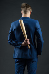 Latent aggression. Businessman or man in formal suit hides wooden bat behind back, dark background. Hidden danger concept. Man with bat hides his aggression slow down and keep calm, rear view