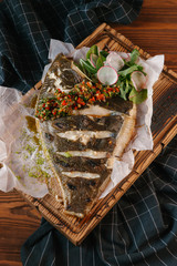 Roasted fish with spices served with herbs and radish on wooden board