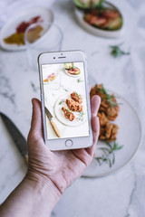 Crop hand taking picture of food
