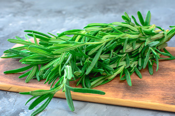 Fresh rosemary bunch on a cutting board. Herbs and spices cooking on stone table.