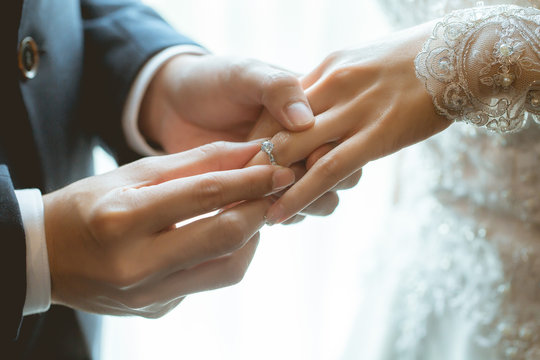 Couple wearing wedding ring at wedding day of them.