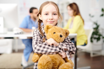 Portrait of cute little girl posing in doctors office smiling happily and hugging teddy bear while looking at camera