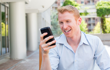 Closeup portrait, young happy businessman in blue shirt sitting, checking his cellphone, isolated on background of a city building, trees, on a sunny autumn day. corporate life success.