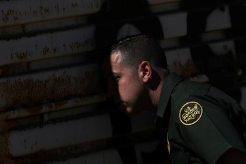 Border patrol agent looks toward Mexico though hole in wall along U.S. border in Tecate, California