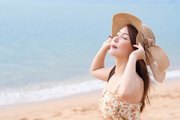 Young Asian woman with hat enjoying at the beach. Summer,vacation and holiday concept