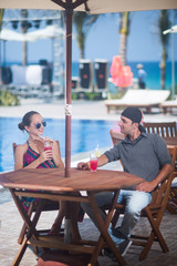 the girl and the man drink a cocktail at the table on the background of the pool and the sea