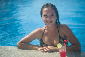 beautiful girl with a drink in a luxurious pool