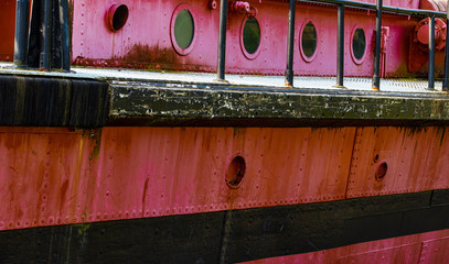 Portholes and deck on an old red rusty boat