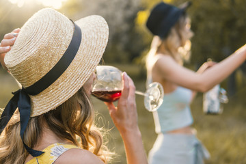 Group of girls friends making picnic outdoor. They have fun and drink wine