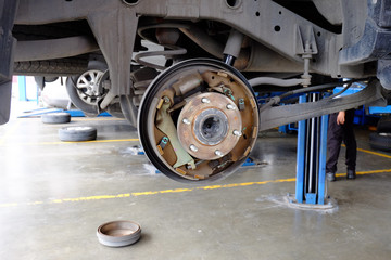 Disc break on car in process to new replacement. Car repairing shop.