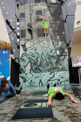 Attendees play on a Spiderman display at E3, the world's largest video game industry convention in Los Angeles