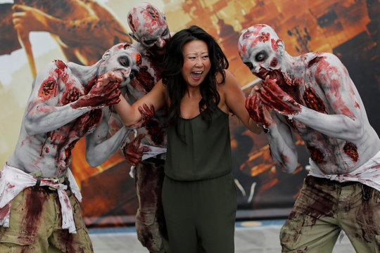 An attendee poses for a picture with zombies at E3, the world's largest video game industry convention in Los Angeles