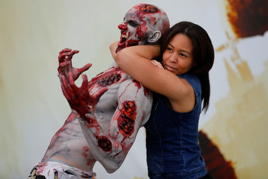 An attendee poses for a picture with a zombie at E3, the world's largest video game industry convention in Los Angeles