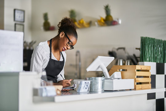 shop assistant taking order on notepad at restaurant counter
