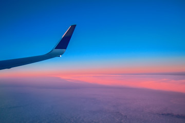 Landscape sunrise over the clouds seen from the window of a flying passenger airliner. View of the wing aircraft. Air travel.