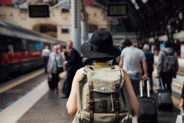 Backside of young backpacker hipster woman walking in the train station. Summer vacation concept.