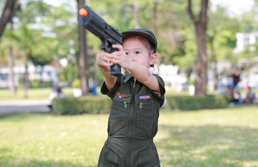Little Asian child girl in pilot soldier suit costume with holding gun in hands at the garden.