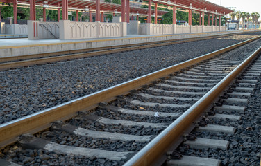 Angled view of empty locomotive train tracks at a station platform at sunset