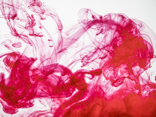 Process of dissolving acrylic ink into water. Amazing abstract background. Splash of colourful paint photographed while in motion. Acrylic cloud in liquid. Droplet of red color dissipation in liquid