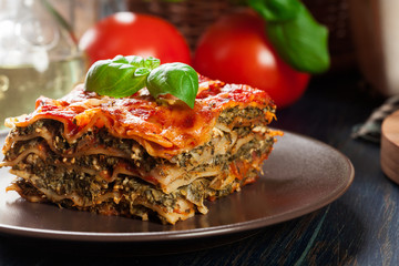 Piece of tasty hot lasagna with spinach on a plate