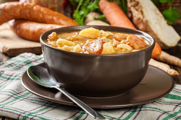 Traditional Polish split pea soup with sausage, bacon and potatoes
