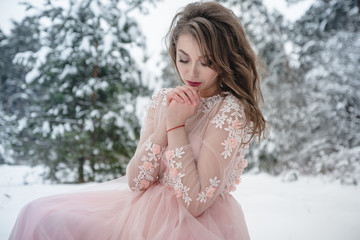 Girl in a beautiful pink dress in a winter forest