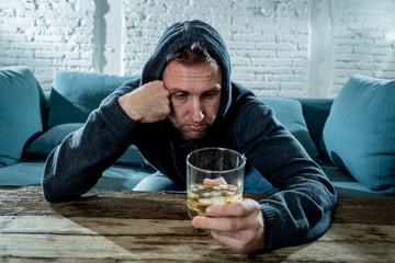 young drunk man depressed and sad drinking whiskey at home